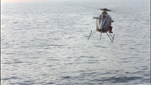 MEDIUM ANGLE OF BLACK HELICOPTER FLYING AWAY FROM CAMERA OVER OCEAN OR SEA WATER. CAMERA PANS RIGHT WITH HELICOPTER UNTIL HELICOPTER DISAPPEARS BEHIND WALL OF SHIP.