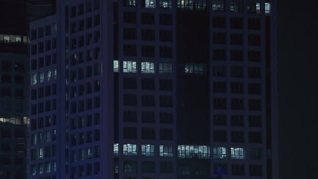 medium angle of white high rise building with glass windows  in city. could be office building. see other high rise building and night time sky in background. - fensterfront stock-videos und b-roll-filmmaterial
