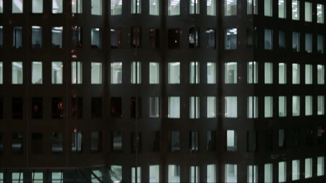 stockvideo's en b-roll-footage met medium angle pan up of office building as if on elevator from distance. building is high-rise with many windows across. windows on some floors are lit up, some are not. reflection of hyatt sign on windows. - hyatt