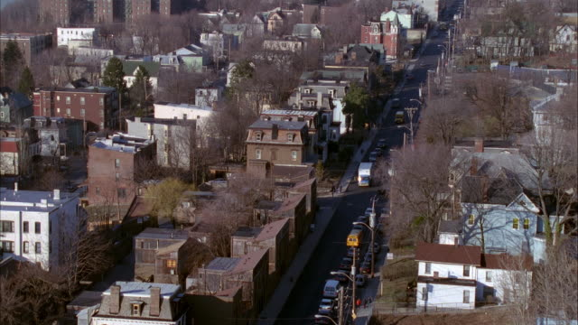 vídeos de stock, filmes e b-roll de pan up from residential area or neighborhood with lower class buildings to see tall building, possibly apartment building, with water and peninsula in background. probably brooklyn or queens. - queens new york city