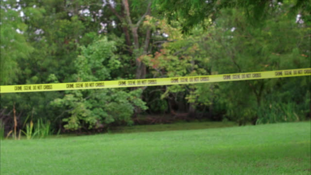 stockvideo's en b-roll-footage met wide angle of police tape crime scene do not cross. trees and brush or forest or woods and large lawn. could be yard. - afzetlint