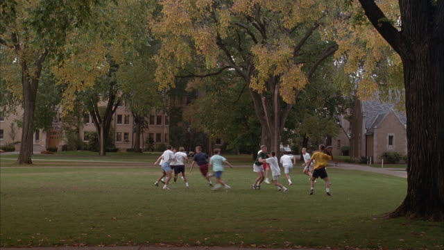 MEDIUM ANGLE OF MEN PLAYING FOOTBALL ON COLLEGE OR UNIVERSITY CAMPUS. QUARTERBACK STEPS BACK, PUMPS, THEN THROWS BALL TO RECEIVER. RECEIVER CATCHES BALL, SLIPS AND FALLS, THEN GETS BACK UP AND IS TACKLED.