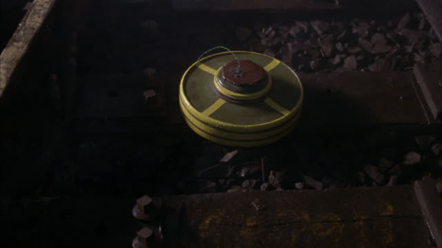 pan up from railroad or subway tracks. see land mines or bombs wired along tracks. lights flash in background. smoke in foreground. could be subway tunnel. - land mine stock videos and b-roll footage