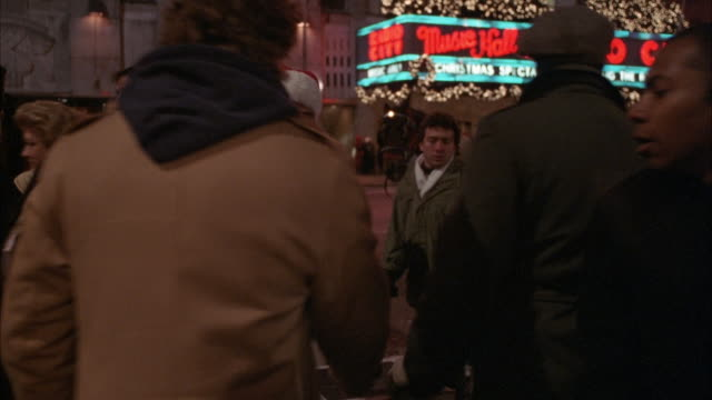 MEDIUM ANGLE OF FRONT OF RADIO CITY MUSIC HALL, SEE NEON SIGN IN BACKGROUND. MAN DRESSED AS SANTA CLAUS RINGS BELL FOR COLLECTION, PEOPLE COME BY AND DROP DONATIONS IN BOX. CHRISTMAS.