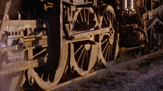 static close up of moving steam engine train lower mechanical/carriage portion on railroad tracks, with steam seen venting from area. train moves, right to left, through frame. - 1923年点の映像素材/bロール