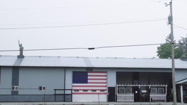 american flag on barn door, car passes, wide - stars and stripes stock videos & royalty-free footage