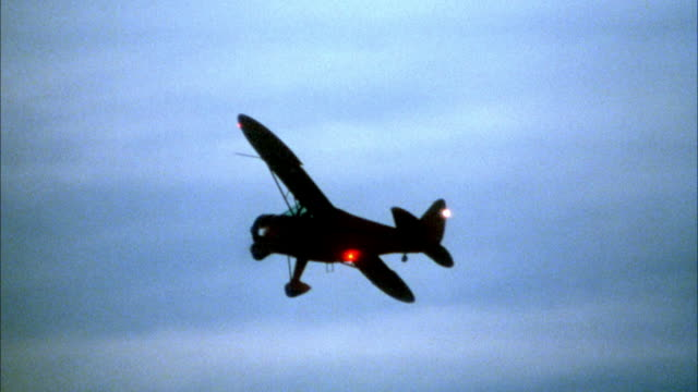 tracking shot of small propeller plane taking off from desert and flying in blue and orange sky. takes off to left, then flies to right. frame loses plane at several points, then pans right to track plane again. - anno 1940 video stock e b–roll
