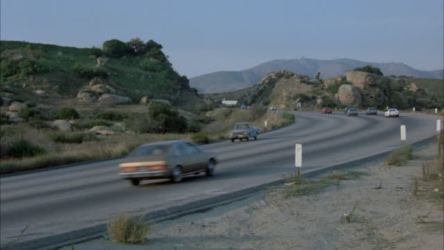 wide shot. freeway with traffic driving in both directions. cars are early 1980's. pov from side of road. bus drives from background to foreground. freeway is surrounded by desert with mountains in background. - 1980 1989 stock-videos und b-roll-filmmaterial