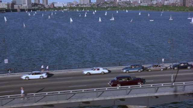 tracking shot of rolls royce limousine driving over bridge on charles river, boston skyline in background. pans up skyline at end. - rolls royce stock videos and b-roll footage