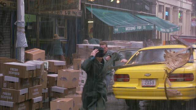 MEDIUM ANGLE OF TAXICAB PULLED UP ALONGSIDE STACKS OF BOXES IN FRONT OF STORES. SEE TWO PEOPLE SUDDENLY FLEE FROM BACK OF TAXI.