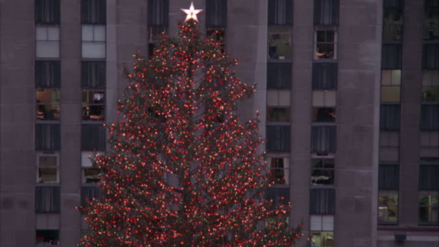 medium angle pan down of giant christmas tree at rockefeller center. see gold statue and ice skating rink at base of christmas tree. people skate as crowd is in front of rink. - rockefeller center stock videos and b-roll footage