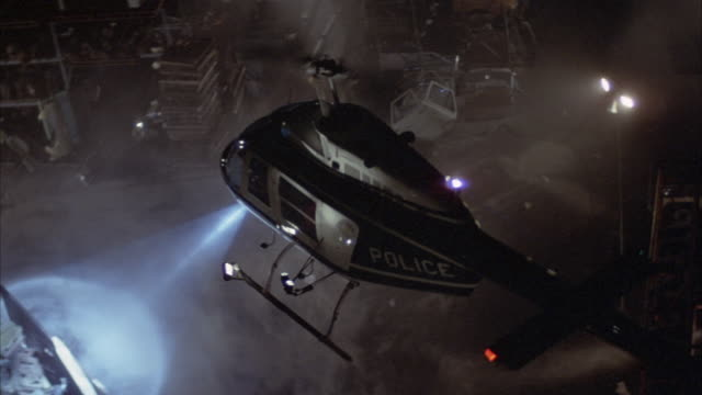 aerial of police helicopter searching with search light in junkyard. - searchlight stock videos & royalty-free footage