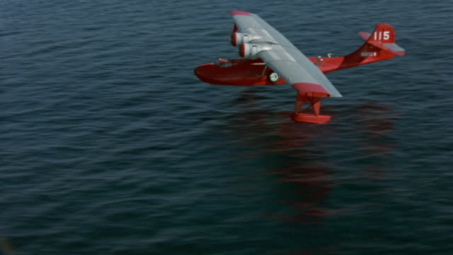 aerial to aerial of red seaplane or water plane landing in water. twin propeller, airplane, aircraft, ocean. - propeller video stock e b–roll