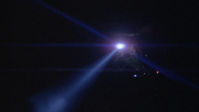 tracking shot of police helicopter with search light on circling overhead. - searchlight stock videos & royalty-free footage