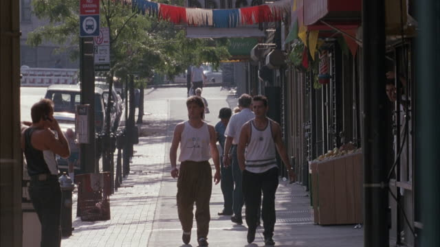 vídeos de stock, filmes e b-roll de medium angle of sidewalk with stores or shops at right. two men in sleeveless shirts smoking cigarettes walk from back and exit right, possibly summer. other people walk on sidewalk. bus driving by obscures view, could be shopping area. - smoking
