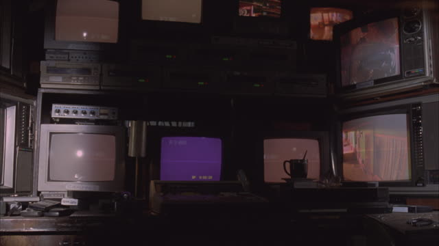 medium angle of 1970s surveillance monitors and video equipment. 1970s televisions stacked on two shelves showing surveillance video feeds. remote controls, video tapes, and coffee cup visible on desk. television in upper right hand corner flickers. - remote control stock videos & royalty-free footage