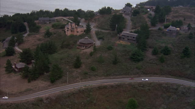 aerial tracking shot of red volkswagen karmen ghia on curvy mountain road. see sea shore ahead and sparse cottages on sides of road. - volkswagen stock-videos und b-roll-filmmaterial