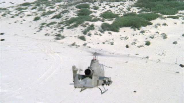 medium angle tracking shot of camouflaged cobra military helicopter flying left to right. arid area or desert with shrubs in background. middle east. attack helicopters. - attack helicopter stock videos and b-roll footage