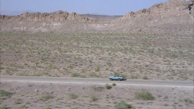 AERIAL TRACKING SHOT OF LIGHT BLUE JEEP ON DESERT HIGHWAY HEADING LEFT. SHRUBS ON SIDES OF ROAD.