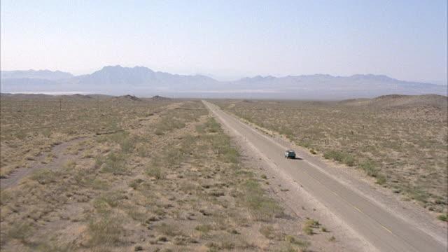 MEDIUM ANGLE ZOOM IN OF LIGHT BLUE JEEP ON DESERT HIGHWAY HEADING LEFT. SHRUBS ON SIDES OF ROAD.