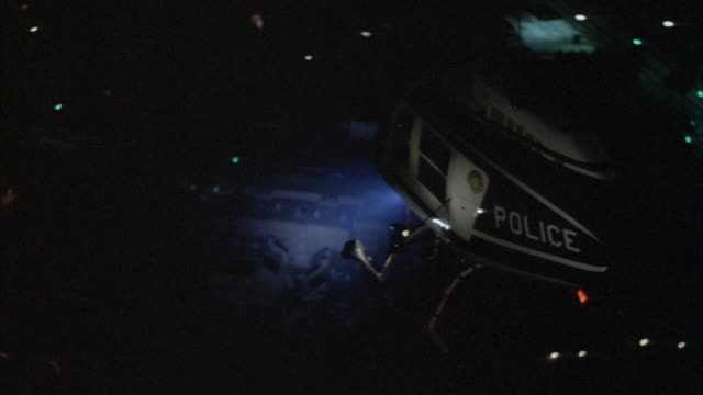 aerial of police helicopter over city. helicopter turns on search light. - suchscheinwerfer stock-videos und b-roll-filmmaterial