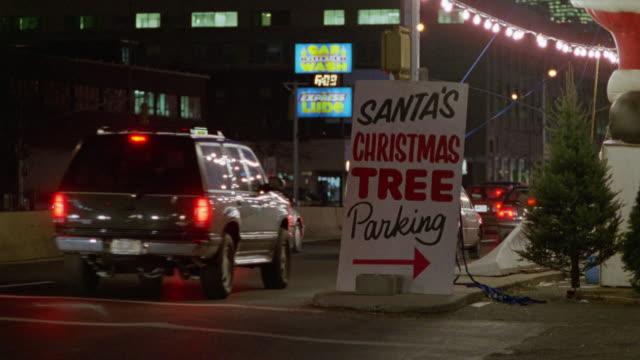 vídeos de stock, filmes e b-roll de close angle of sign reading santa's christmas tree parking in center of city street with traffic. insert. - 1980 1989