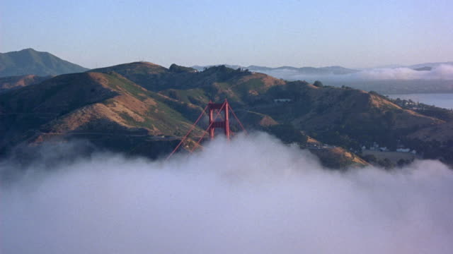 aerial. passing over san francisco bay. flying above golden gate bridge  fog over bridge. pans right of bridge and passes above. shot circles around toward top of clouds. - golden gate bridge stock videos & royalty-free footage