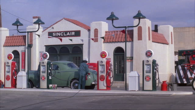 MEDIUM ANGLE OF GAS STATION WITH SIGN SINCLAIR. TWO MEN SERVICE GREEN CARBY GAS PUMP, START RUNNING TO LEFT AS STREETCAR OR TROLLEY CRASHES INTO GAS BUMP AND GREEN CAR. MEN COME BACK, SEE PASSENGERS STANDING IN STREETCAR. NEG CUT.