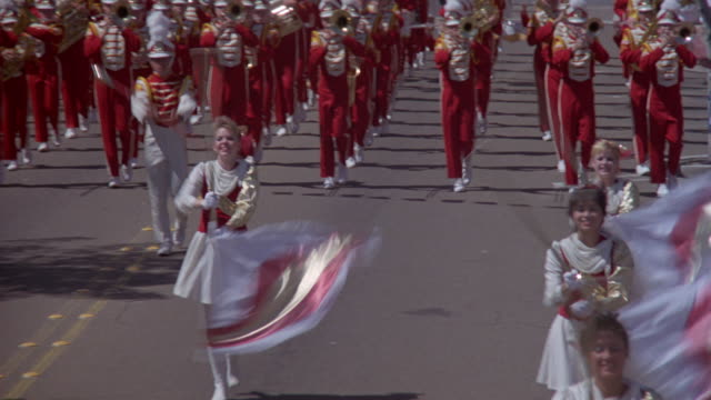 medium angle of parade. band with banner that reads fountain valley high school marches forward, wearing red uniforms. - parade stock videos & royalty-free footage