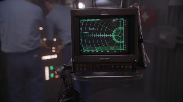 MEDIUM ANGLE OF SMALL SONY TELEVISION WITH A RADAR SYSTEM DISPLAYED ON SCREEN IN CONTROL ROOM. SEE MEN IN NAVY BLUE HATS AND PANTS AND SKY BLUE SHIRTS WORKING ON CONTROL PANEL IN BACKGROUND.