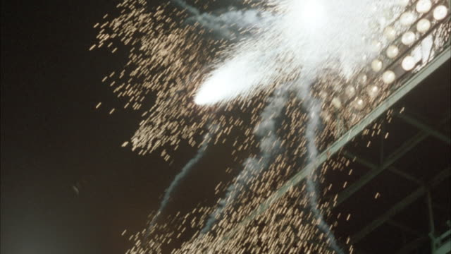 MEDIUM UP ANGLE SHOT OF BASEBALL STADIUM'S  SINGLE SET OF NIGHT LIGHTS, 1940'S PERIOD TYPE. LIGHTS SEEN ON, THEN EXPLODE IN BURST OF SPARKS AND FIREWORKS-LIKE FLARES WITH ACCOMPANYING SMOKE.