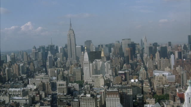 vídeos de stock, filmes e b-roll de aerial of midtown manhattan skyscrapers, pov from south looking north. starts on empire state building and pulls back to wider angle new york city skyline. - new york city
