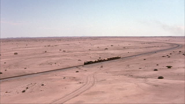 aerial of steam engine train traveling through barren, desolate desert landscape. camera moves towards steam engine to pass over smoke stack and locomotive of train. see many train cars pass by and railway. - locomotive stock-videos und b-roll-filmmaterial