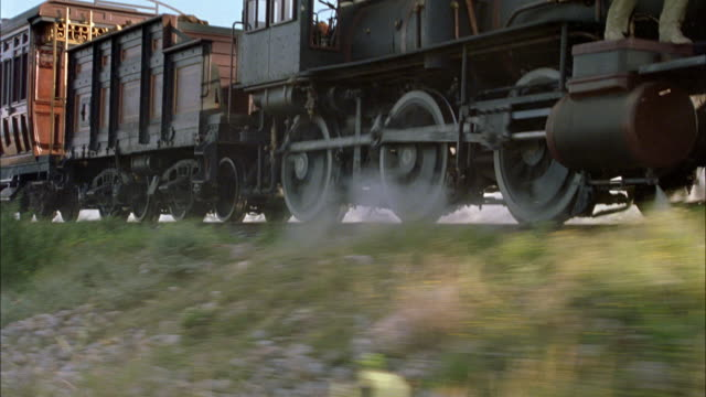 medium angle of steam engine train wheels. see train drive left to right. see bushes or shrubs in foreground. train could be passing desert area. - locomotive stock videos & royalty-free footage