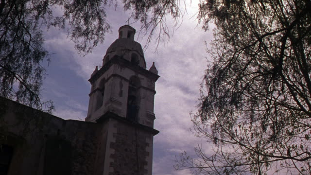 up angle of tower building in mexico. could be catholic church or monastery or cathedral or convent. large wispy tree frames the shot around top and sides. - monastery stock videos & royalty-free footage