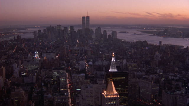 aerial of manhattan and new york city skyline, moves back to empire state building. world trade center twin towers. reddish or orange sky at right. - world trade center manhattan video stock e b–roll