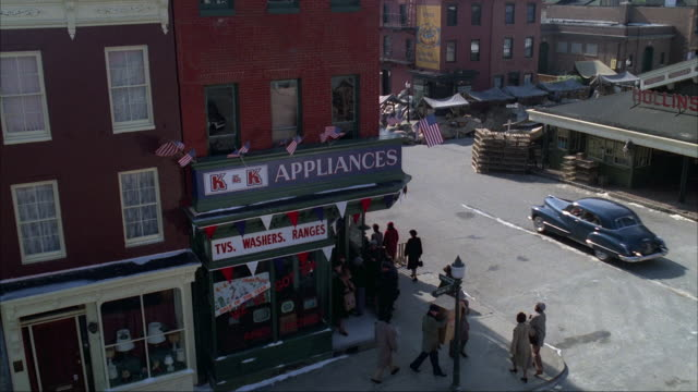vídeos de stock, filmes e b-roll de medium high angle down of street corner by marketplace. sign reads k&k appliances with crowd lined outside store. pans right to alleys of marketplace with canopies. market sign reads hollins market. - baltimore maryland