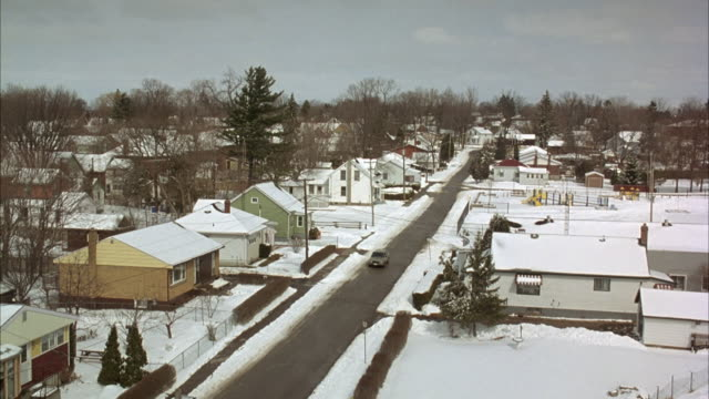 HIGH ANGLE DOWN OF TOWN STREET IN SMALL TOWN RESIDENTIAL AREA. DURING WINTER, SNOW ON GROUND. RANCH STYLE HOUSES AND ONE TWO STORY, MIDDLE CLASS.