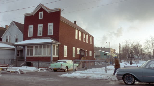medium angle establish of two story or three story, could be two story with attic. turquoise classic car parked in driveway. three people walk by on street, pickup truck drives by on street. snow on ground, winter. - anno 1955 video stock e b–roll