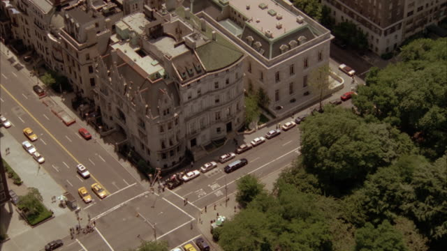 aerial of four story brownstone apartment building with castle-like style on city street corner. pov slowly moves around building showing both sides facing street. see other apartment buildings to side of featured building. see park across street. - 1999 stock videos & royalty-free footage