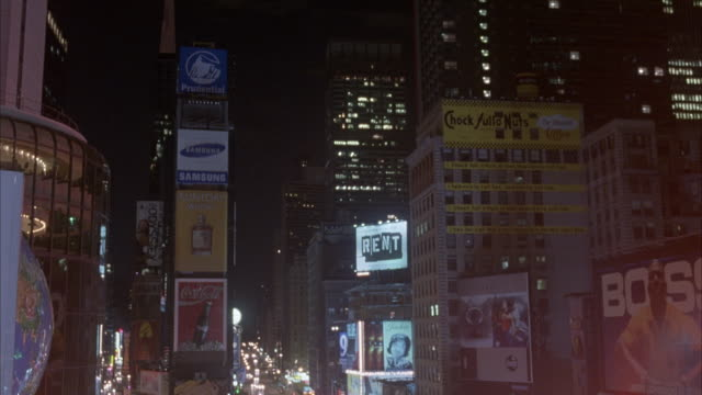 PAN LEFT TO RIGHT OF TIMES SQUARE AT NIGHT. BUSY TRAFFIC ON CITY STREET BELOW. SEE RENT ON SIGN IN BACKGROUND. SEE BILLBOARDS. POV FROM HIGH RISE BUILDING.