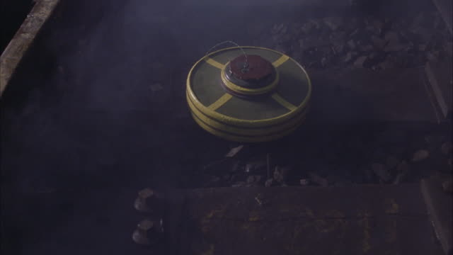pan up from railroad or subway tracks. see land mines or bombs wired along tracks. lights flash in background and smoke in foreground. could be subway tunnel. - land mine stock videos and b-roll footage