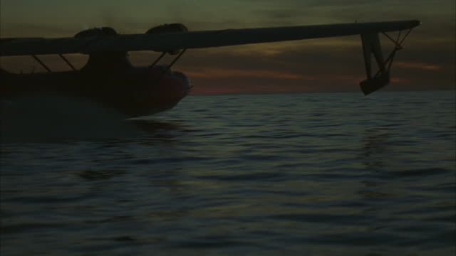 WIDE ANGLE OF SMALL DUAL PROPELLER RED AIRPLANE TAKING OFF OR PERFORMING TAKE-OFF IN OCEAN OR SEA AT DUSK. SEE WATER SPLASH UNDERNEATH AS WATER PLANE ACCELERATES AND BEGINS FLYING AWAY FROM CAMERA.