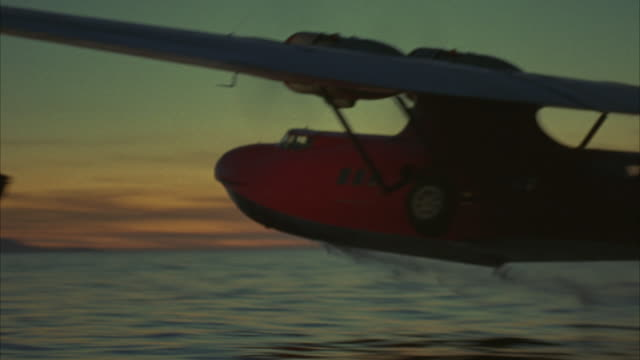 wide angle of small dual propeller red airplane taking off or performing take-off in ocean or sea at dusk. see water splash underneath as water plane accelerates and begins flying away from camera. - propeller video stock e b–roll