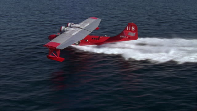 aerial of small dual propeller red airplane taking off or performing take-off in ocean or sea from right to left. see water splash underneath as water plane accelerates and begins flying. - propeller video stock e b–roll
