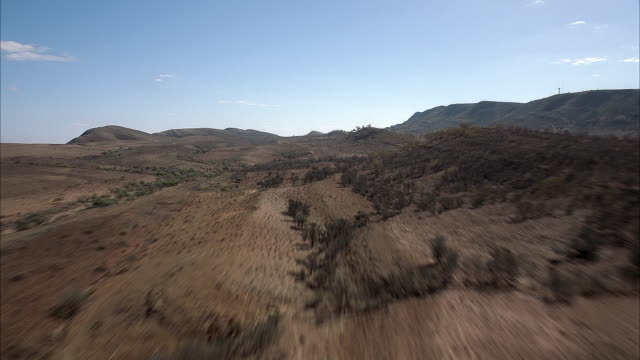 vídeos y material grabado en eventos de stock de front moving aerial through plains of desert and hills. dense shrubs and vegetation on hills, valleys, and plains. close angle of mountain slope at end, shot swerves left. - oceania
