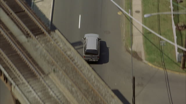 aerial tracking shot of silver mercedes down street in urban area as it weaves through traffic. see car cross under several freeway overpasses. - mercedes benz stock videos and b-roll footage