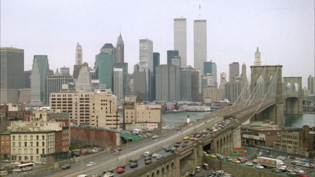 wide angle of new york city skyline. see twin towers. see several crossing freeways in foreground. see traffic jammed on right side of top freeway and on both sides of bottom freeway. - 1996 video stock e b–roll