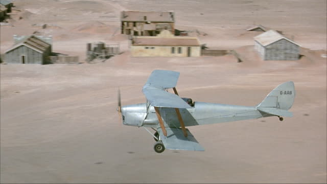 aerial air-to-air tracking shot of small single propeller biplane circling over small desert town for landing. see airplane swoop past camera to land on dirt path behind town. - 複葉機点の映像素材/bロール