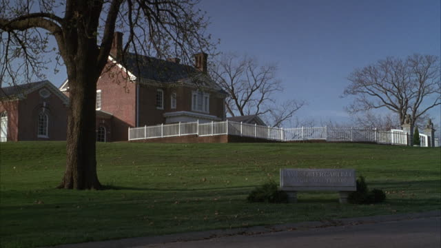 established medium angle of james greer carlisle presidential library on grass lawn. two story colonial brick house or former plantation. some bare trees. - zweistöckiges wohnhaus stock-videos und b-roll-filmmaterial